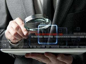 Inspecting a tablet magnifying glass businessman