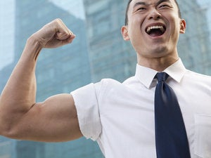portrait of young businessman flexing muscle outdoors 169277329