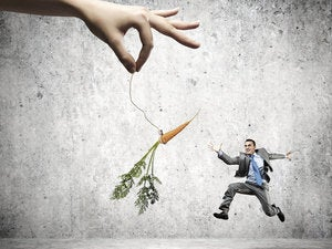 Businessman chasing a dangling carrot.