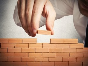 Man building miniature brick wall