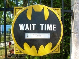 A sign that looks like the Batman logo that says Wait Time