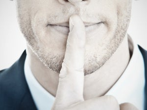 Man holding finger up to mouth to be quiet