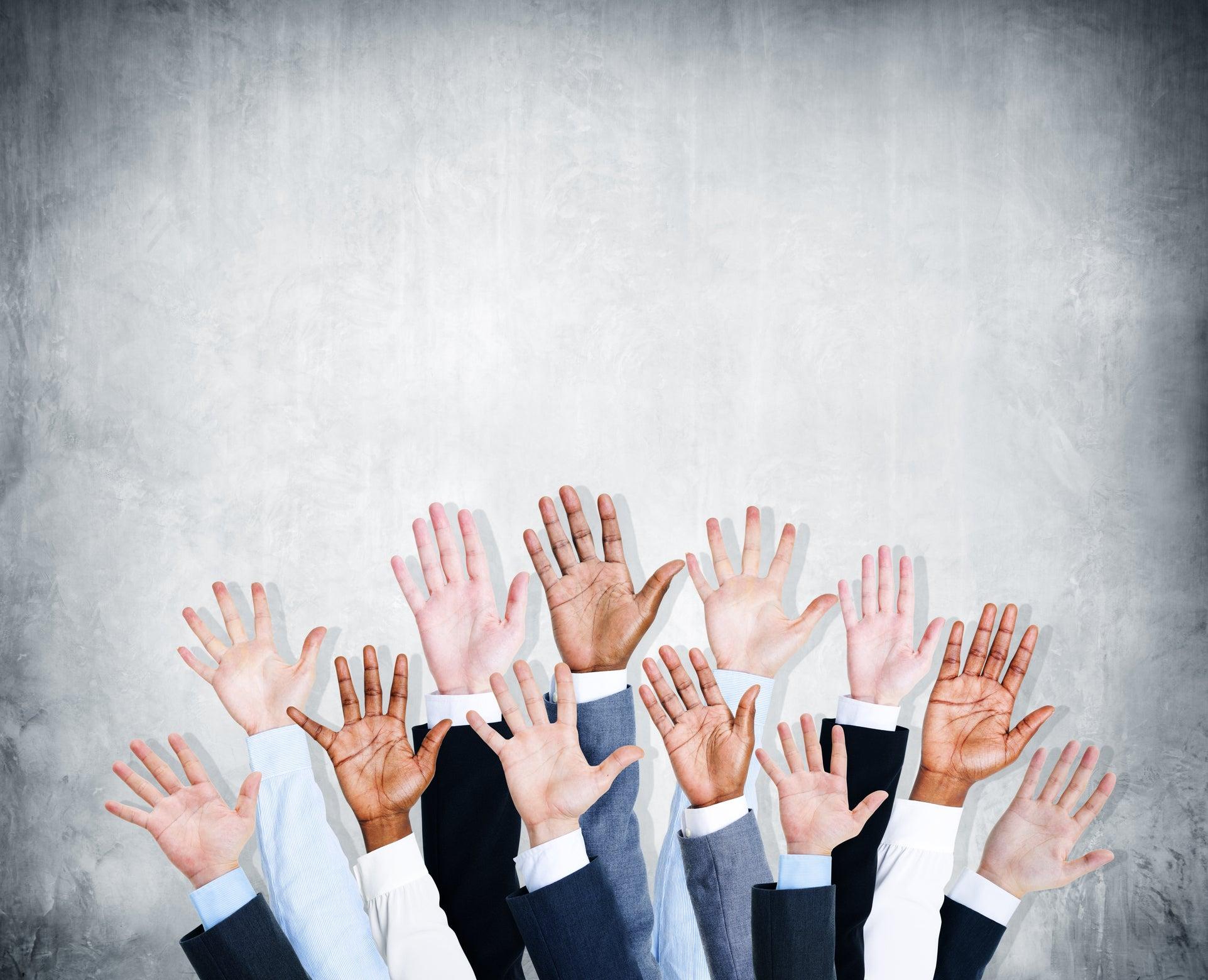 Group of hands raised to volunteer