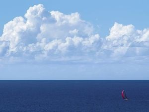 yacht with red spinnaker at full sail on blue ocean with clouds